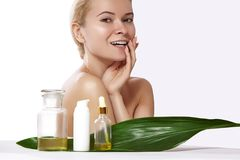 De mooie glimlachende vrouw vraagt organische schoonheidsmiddel en oliën schoonheid aan Kuuroord en wellness Schone huid, glanzen royalty-vrije stock afbeeldingen