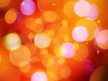 De mooie gloeiende sinaasappel vage lichten schitterende warme samenvatting met schittert effect stock afbeelding