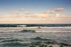 De mooie golven wassen het strand met gouden zand vóór zonsondergang Dramatische scène stock foto's