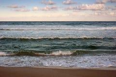 De mooie golven wassen het strand met gouden zand vóór zonsondergang Dramatische scène stock fotografie