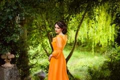 De mooie gravin in een lange oranje kleding Royalty-vrije Stock Foto's