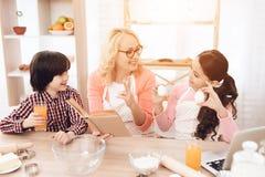 De mooie grootmoeder in schort, samen met haar kleinkinderen, bekijkt kookboek in keuken stock fotografie