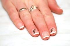 De mooie hand van de vrouw met geschilderde witte spijkers Royalty-vrije Stock Afbeeldingen