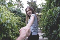 De mooie hand van de vrouwenholding van haar vriend in het park stock fotografie