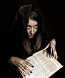 De mooie heks giet werktijden van dik oud boek door kaarslicht op een donkere achtergrond Royalty-vrije Stock Afbeelding