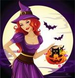 De mooie heks houdt een grappige pompoen Stock Foto