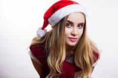 De mooie het glimlachen hoed van de Kerstman van de vrouwenslijtage en geleund naar de camera om iets te zeggen Meisje gelukkig g stock foto