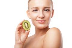 De mooie het glimlachen kiwi van de vrouwenholding. Schoonheidsschot Stock Afbeeldingen