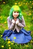 De mooie hipster alternatieve jonge vrouw met geel haar zit in gras met paardebloem in park stock foto