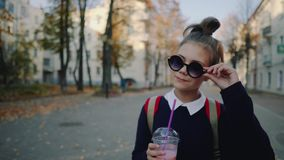 De mooie hipstertiener met rode zak drinkt milkshake van een plastic kop het lopen straat tussen gebouwen Leuk meisje binnen stock footage