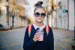 De mooie hipstertiener met rode zak drinkt milkshake van een plastic kop het lopen straat tussen gebouwen Leuk meisje binnen stock foto's