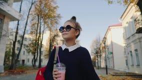 De mooie hipstertiener met rode zak drinkt milkshake van een plastic kop het lopen straat tussen gebouwen Leuk meisje binnen stock video