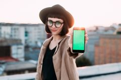 De mooie hipstervrouw houdt smartphone aan camera stock afbeeldingen