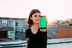 De mooie hipstervrouw houdt smartphone aan camera stock afbeelding