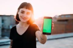 De mooie hipstervrouw houdt smartphone aan camera stock foto