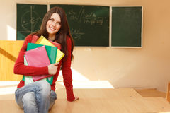 De mooie hoge uitvoerder van het tienermeisje in klaslokaal dichtbij bureau gelukkig s Royalty-vrije Stock Afbeeldingen