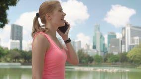 De mooie jogging van de vrouwenagent in park Geschikte vrouwelijke sportfitness opleiding Het spreken op haar smartphone stock videobeelden