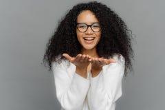 De mooie jonge Afrikaanse Amerikaanse die vrouw verzendt luchtkus, houdt palmen dichtbij mond worden uitgerekt, toont witte tande royalty-vrije stock afbeelding