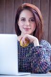 De mooie jonge appel van de vrouwenholding dichtbij haar laptop op wonde Royalty-vrije Stock Afbeeldingen