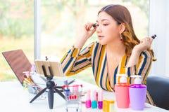 De mooie jonge Aziatische vrouw die haar zetten maakt omhoog tijdens haar online overzicht van het schoonheidsproduct thuis royalty-vrije stock foto