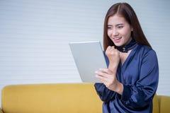 De mooie jonge Aziatische vrouw wekte het bekijken het digitale glimlachende meisje van de tabletcomputer met aanrakingsstootkuss stock afbeeldingen
