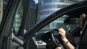 De mooie jonge bankiers belangrijkste onderneemster gaat zitten in auto op megalopolisstraat stock video