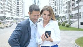 De mooie jonge bedrijfsdame toont interessante opties op haar telefoon aan een bedrijfsmens en bespreekt ontwikkelingswegen stock videobeelden