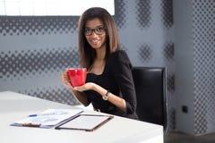 De mooie jonge bedrijfsdame in zwarte sterke reeks zit bij de bureaulijst, greep rode kop Royalty-vrije Stock Foto