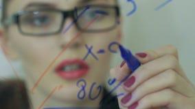 De mooie jonge bedrijfsvrouw voert financiële berekeningen uit stock video
