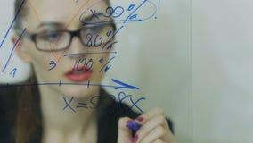 De mooie jonge bedrijfsvrouw voert financiële berekeningen uit stock footage