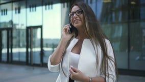De mooie jonge belangrijkste bankiersvrouw spreekt op telefoon die zich op achtergrond van de bureaubouw bevinden stock video