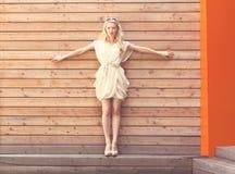 De mooie jonge bevindende die handen van de blondevrouw op de achtergrondmuur van houten planken worden uitgespreid Gestemd in wa Royalty-vrije Stock Foto