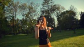 De mooie jonge blazende zeepbels van de redhairvrouw in openlucht stock videobeelden