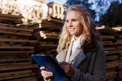 De mooie jonge blonde bedrijfsdame schrijft resultaten in openlucht van inspectie Stock Foto's