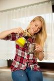 De mooie jonge blonde vrouw kookt koffie in keuken Royalty-vrije Stock Afbeelding