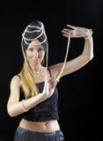De mooie jonge blondevrouw met lang haar en een parel danst een oosterse dans op donkere achtergrond Stock Foto's