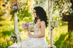 De mooie jonge bruid, model donkerbruin meisje in witte die kleding, zit op een schommeling met bloemen wordt verfraaid stock afbeeldingen