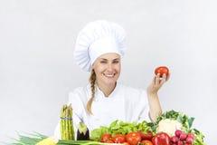 De mooie jonge chef-kokvrouw treft en binnen verfraaiend smakelijk voedsel voorbereidingen Stock Fotografie