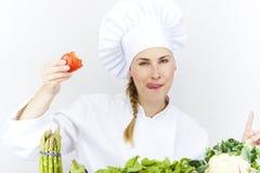 De mooie jonge chef-kokvrouw treft en binnen verfraaiend smakelijk voedsel voorbereidingen Royalty-vrije Stock Foto