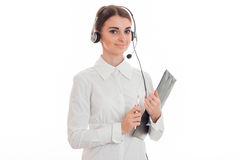 De mooie jonge donkerbruine die vrouw van de vraagbeambte met hoofdtelefoons en microfoon op witte achtergrond wordt geïsoleerd Royalty-vrije Stock Afbeelding