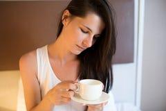 De mooie jonge donkerbruine vrouw drinkt koffie in de ochtend, op w Royalty-vrije Stock Fotografie