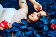 De mooie jonge donkerbruine vrouw in witte kleding ligt op fantastische blauwe kleurenbladeren en bloemen Fantastisch landschap Royalty-vrije Stock Afbeeldingen