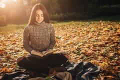 De mooie jonge donkerbruine zitting op de gevallen herfst gaat in een park, lezing een weg boek Royalty-vrije Stock Afbeeldingen