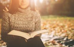 De mooie jonge donkerbruine zitting op de gevallen herfst gaat in een park, lezing een weg boek Stock Foto