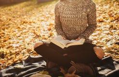 De mooie jonge donkerbruine zitting op de gevallen herfst gaat in een park, lezing een weg boek Stock Afbeeldingen