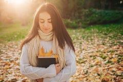 De mooie jonge donkerbruine zitting op de gevallen herfst gaat in een park, lezing een weg boek Royalty-vrije Stock Foto's