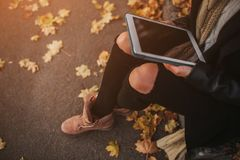 De mooie jonge donkerbruine zitting op de gevallen herfst gaat in een park, lezing een weg eBook op een tabletcomputer Stock Foto