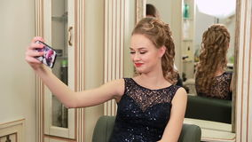 De mooie, jonge en sensuele vrouw met mooie samenstelling en elegant kapsel in avondjurk neemt selfie en kijkt aan smartp stock video