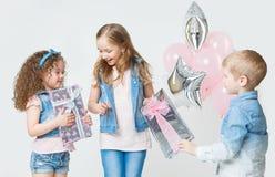 De mooie jonge geitjes bij verjaardagspartij het geven stelt in jeanskleren voor ballons Het glimlachen Stock Afbeelding