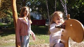 De mooie jonge gelukkige moeder slingert haar dochter in een park op een schommeling 4K Langzame Motie stock video